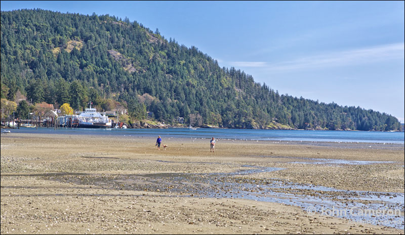 Boaters walk the Fulford beach at low tide.