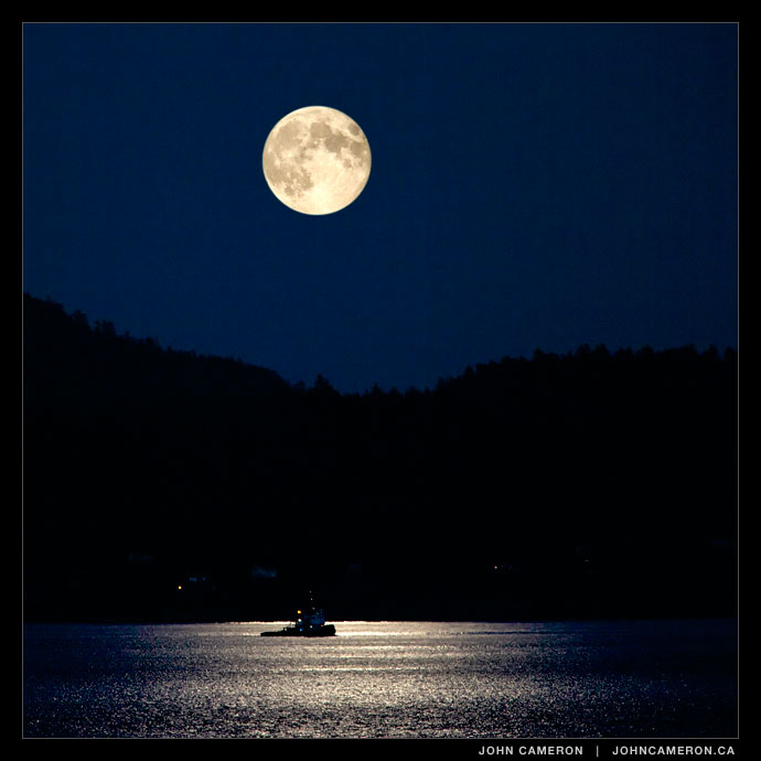 A tug works under a full moon near Pender Islands