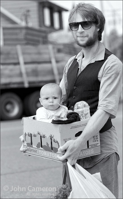 baby in a tomato box at the salt spring market